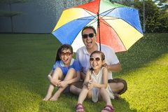 Father and two daughters sitting on a meadow with colorful umbre Royalty Free Stock Photo