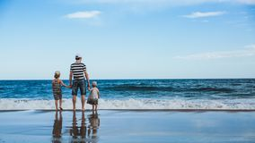 father and two daughters standing at the beach royalty free stock images