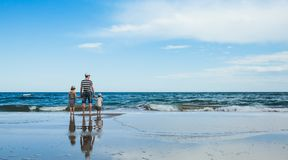 father and two daughters standing at the beach royalty free stock photography