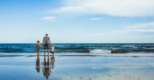 father and two daughters standing at the beach stock images