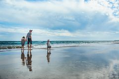 father and two daughters standing at the beach stock image