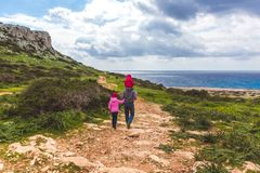 Father and two daughters walk along the path along the sea. Beautiful valley by the sea. Seascape in Cyprus Ayia Napa royalty free stock images