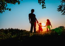 Father with two daughters walk at sunset nature. Parenting stock image