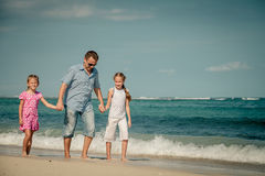 Father and two daughters walking on the beach Royalty Free Stock Photography