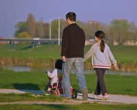 Father And Two Dothers. Walking at the promenade down the river shore Royalty Free Stock Images