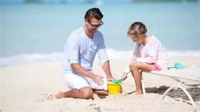 Father and his little daughter playing with sand and making sand castle on tropical beach. Father and two girl playing with sand on tropical beach stock footage