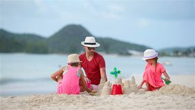 Father and two girls playing with sand and making sand castle on tropical beach. Father and two girls playing with sand on tropical beach stock footage