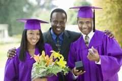 Father with two graduates outside. Portrait