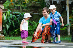 Father and two kids at Bali temple royalty free stock images