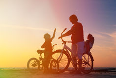 Father with two kids on bikes at sunset Stock Photography
