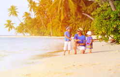 Father and two kids collecting shells on beach Royalty Free Stock Images