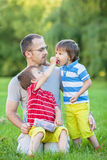 Father with two kids, eating cherries Stock Images