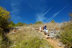 Father and two kids having fun hiking on warm and sunny summer day during family vacations in Zagoria, Greece royalty free stock photography