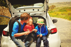 Father with two kids looking at map while travel by car Stock Photography