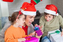 Father with two kids open christmas presents Royalty Free Stock Images