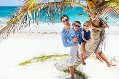 Father and two kids on palm. Father and two kids sitting on palm at Caribbean beach stock image