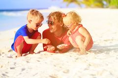 Father and two kids playing with sand on beach. Father and kids playing with sand on beach, family vacation Stock Photo