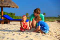 Father and two kids playing with sand on the beach. Father and two kids playing with sand on summer beach Royalty Free Stock Images