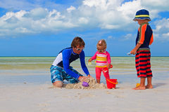 Father and two kids playing with sand on the beach. Father and two kids playing with sand on summer tropical beach Stock Image