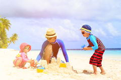 Father and two kids playing with sand on beach. Father and two kids playing with sand on summer tropical beach Royalty Free Stock Photo
