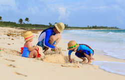 Father and two kids playing with sand on summer. Tropical beach Stock Photos