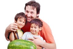 father and two kids preparing watermelon Stock Image