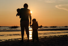 Father and two kids silhouettes on sunset beach. Father and two kids silhouettes on the beach at sunset, family concept stock photos