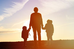 Father and two kids travel at sunset Royalty Free Stock Photography