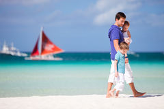 Father and two kids walking along the beach Stock Images