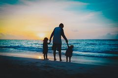 Father and two kids walking on beach at sunset. Parenting stock photography