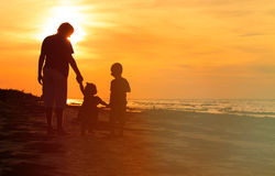 Father and two kids walking on beach at sunset Stock Photography