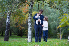 Father and two kids walking in a forest on an autumn day Stock Image
