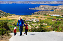 Father with two kids walking on scenic road Stock Photography
