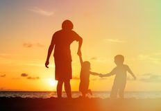 Father and two kids walking at sunset Royalty Free Stock Images