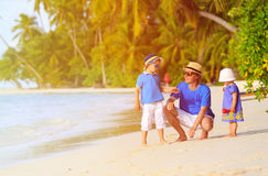 Father and two kids walking on tropical beach Stock Photo