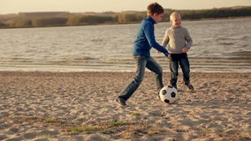 Father and two little boys playing football on the. Beach of the lake at sunset stock video footage