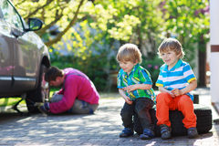 Father and two little boys repairing car and changing wheel toge Royalty Free Stock Photo