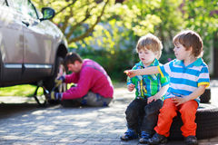 Father and two little boys repairing car and changing wheel toge Royalty Free Stock Image