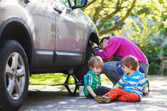 Father and two little boys repairing car and changing wheel toge Royalty Free Stock Photos