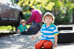 Father and two little boys repairing car and changing wheel toge Stock Image