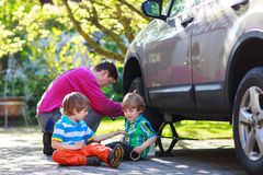 Father and two little boys repairing car and changing wheel toge Stock Photo