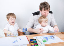 Father and two little boys siblings having fun painting Royalty Free Stock Photos