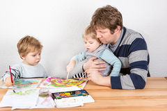 Father and two little boys siblings having fun painting Stock Image