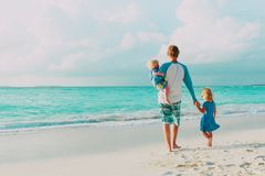 Father and two little daughter walk on beach. Parenting concept royalty free stock photo