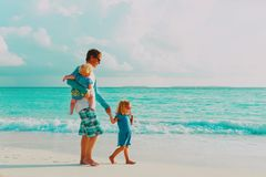 Father and two little daughter walk on beach. Parenting concept stock photo