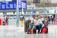 Father and two little sibling boys at the airport Royalty Free Stock Photography