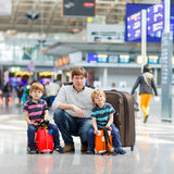 Father and two little sibling boys at the airport Stock Image