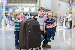 Father and two little sibling boys at the airport Stock Photography