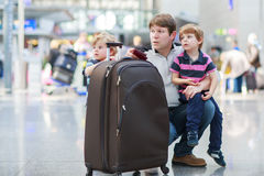 Father and two little sibling boys at the airport Stock Photos