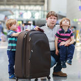 Father and two little sibling boys at the airport Royalty Free Stock Photo